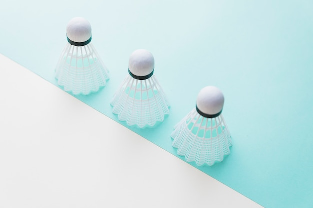 Three white shuttlecock on dual background