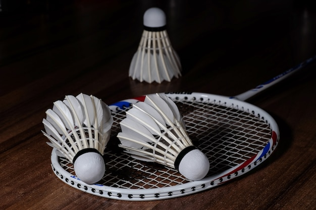 Three white shuttlecocks and a badminton racquet