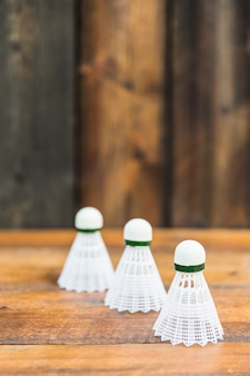 Three white shuttlecocks on wooden table