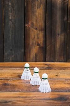Three white shuttlecocks on wooden table