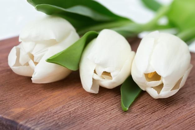 Три белых тюльпана крупным планом на деревянном столе. живые цветы.