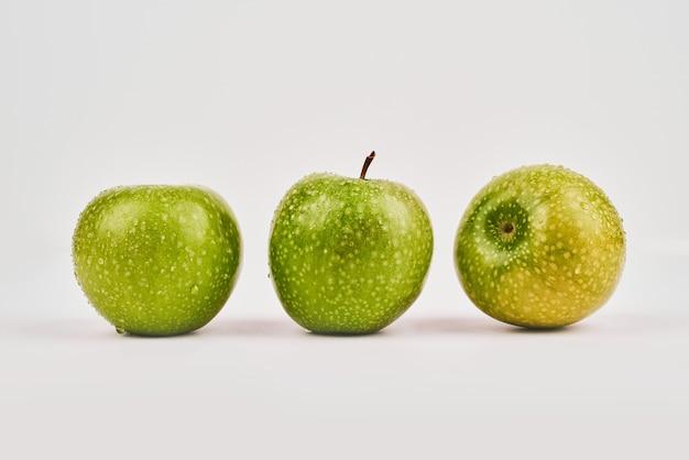 Три целых яблока на белой поверхности.