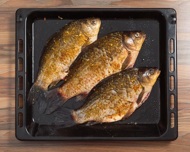 Три целых карась готовятся для запекания в духовке. рыба лежит на противне. свежеочищенная рыба со специями