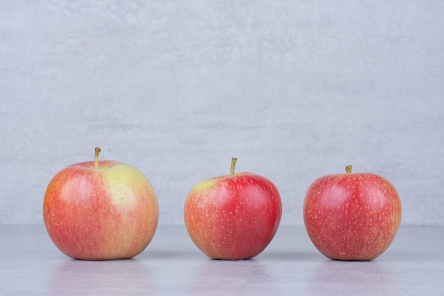 Три целых свежих яблока на белом фоне. фото высокого качества