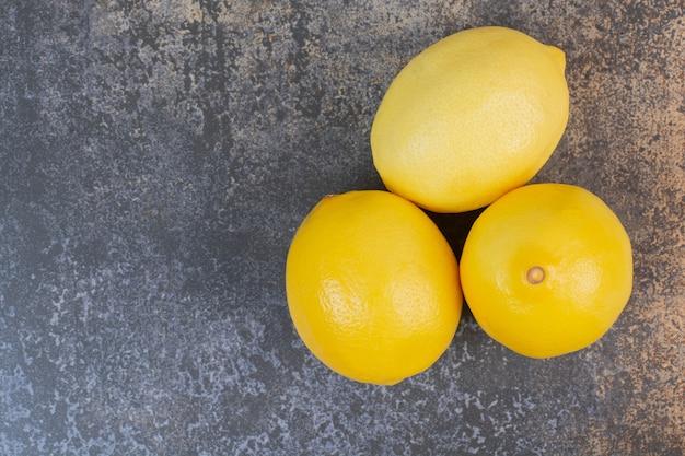 Tre limoni freschi interi su uno spazio di marmo