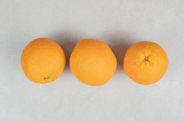 Three whole oranges on gray surface