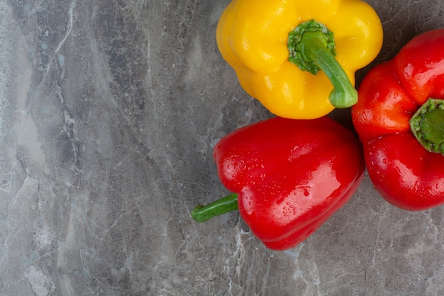 Three whole peppers on marble background