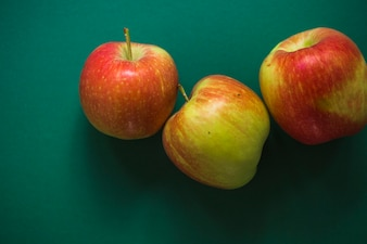 Three whole red apples on green background