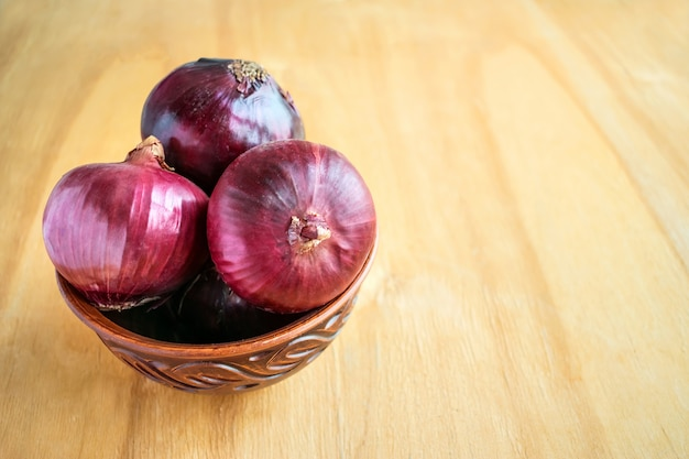 Three whole red onion bulbs in brown rustic bowl