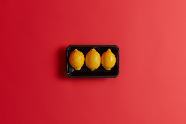 赤いスタジオの背景の上に分離された黒いトレイに3つの全体の黄色の酸っぱいおいしいレモン。ビタミンcが豊富な天然物。健康的な栄養のコンセプト。有機の新鮮な柑橘系の果物。上面図 無料写真