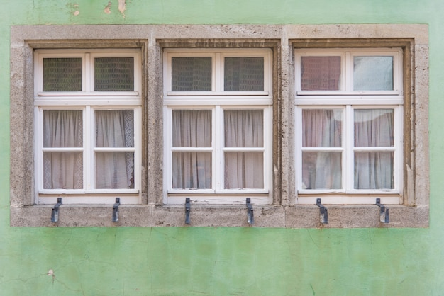 Three windows on classic green old wall in europe