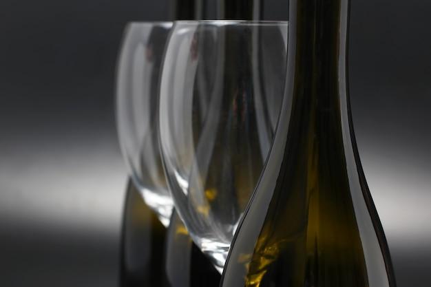 3本のワインボトルと2本の空のワイングラスがクローズアップ