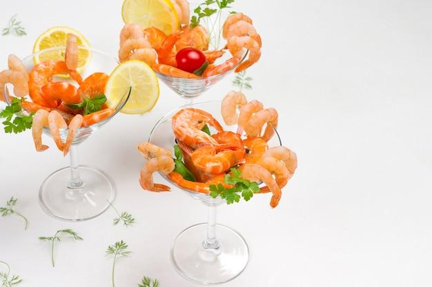 Три бокала с креветками, лимоном и помидорами и зеленью.