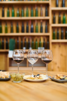 Three wineglasses and snack for sommelier on wooden table inside cellar of luxury restaurant