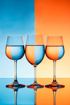 Three wineglasses with water over blue and orange background.