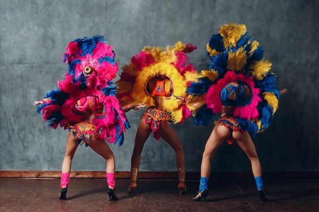 Три женщины в бразильском карнавальном костюме самбы с красочным оперением перьев.