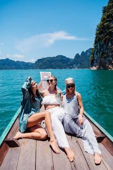 Tre amiche turisti donna viaggiano nel parco nazionale di khao sok, in vacanza in thailandia. navigando sulla barca asiatica sul lago al giorno pieno di sole, con una vista incredibile.