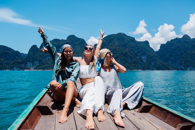 Three woman tourists friends travel around khao sok national park, on vacation in thailand. sailing on asian boat on lake at sunny day, with amazing view.