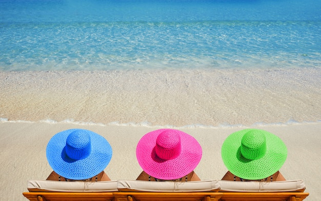 Three women on the beach in bright hats traveling on vacation