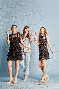 Three women celebrate holiday having fun confetti