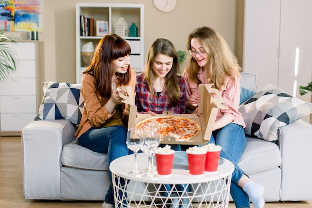 Three women friends having dinner at home. photo of cheerful surprised girls celebrating a party at home, opening cardboard box with with pizza.