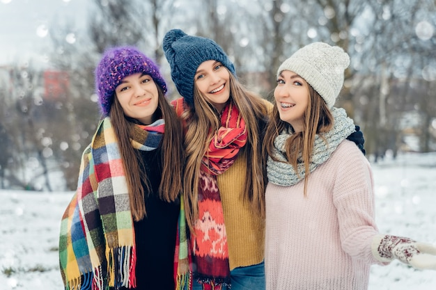 눈 덮인 추운 날씨에 재미 니트 모자에 야외 세 여자 친구