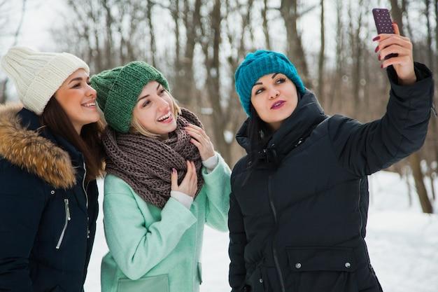 雪の降る寒い冬の天候で、ニットの帽子をかぶった屋外の3人の女性の友人。雪の上で自分撮りを作る暖かい服を着て笑顔の女の子