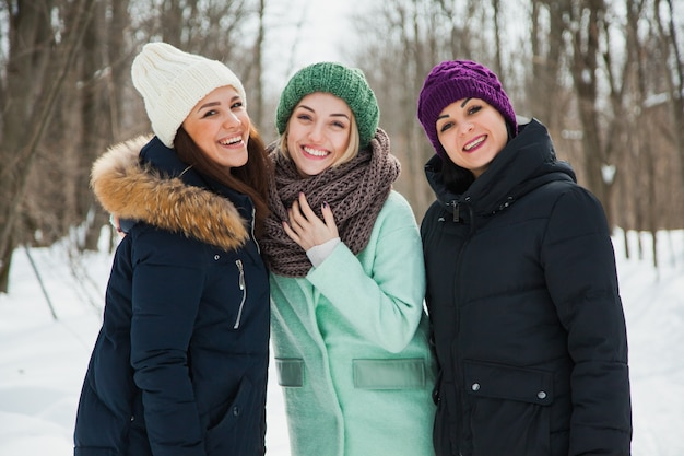 雪の降る寒い冬の天候で、ニットの帽子をかぶった屋外の3人の女性の友人。暖かい服を着て笑顔の女の子。