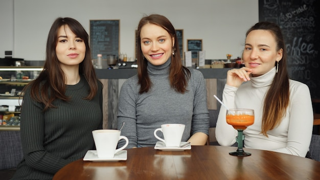 Three women girlfriends with beverages in a cafe are talking