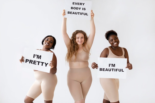 Three women holding placards with body positivity statements