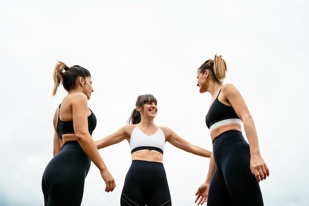 흰색 배경으로 피트니스 세션을 한 후 큰 기쁨으로 서로 포옹하는 세 여성
