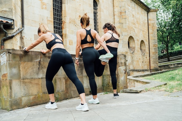 Three women hugging each other with great joy after doing a fitness session with a white background