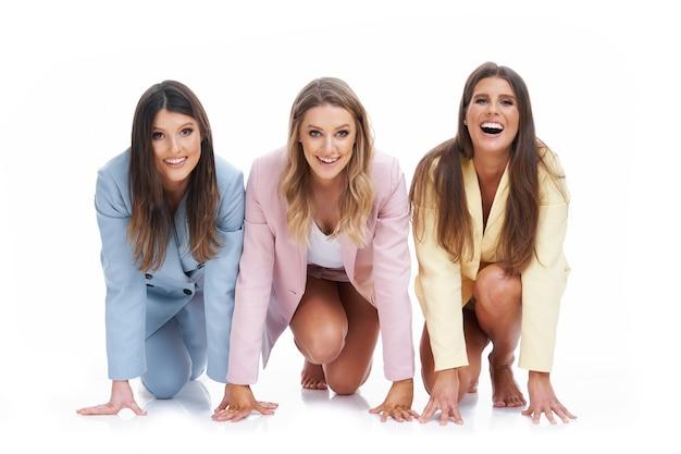 Три женщины в пастельных костюмах позируют на белом фоне