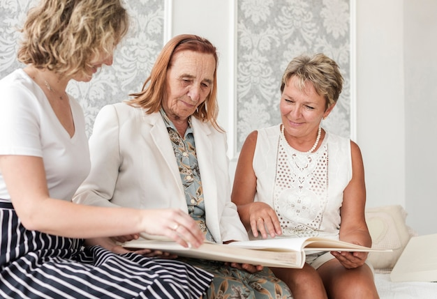 Three women looking at family photo album while sitting on sofa at home