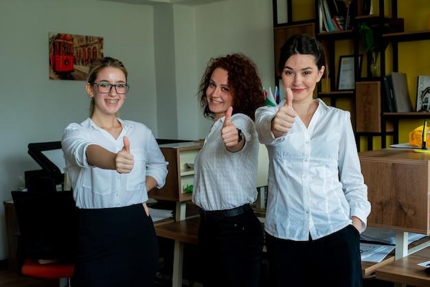 Tre donne impiegati in ufficio guardando la telecamera sorridendo allegramente mostrando i pollici in su lavorando insieme in piedi in ufficio
