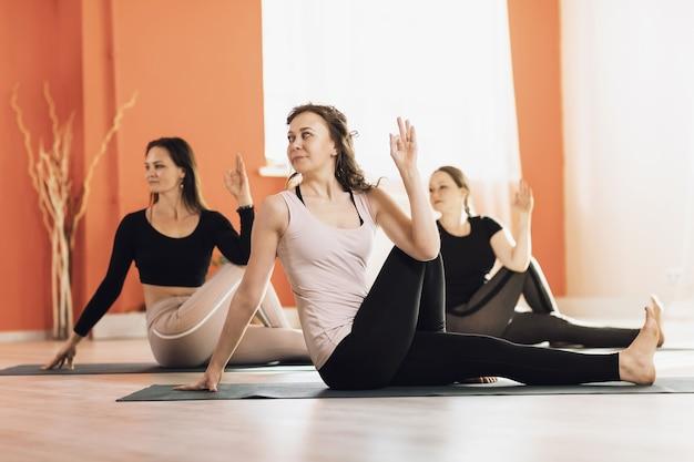 Три женщины, практикующие универсальную йогу, выполняют упражнение ардха матсиендрасана с прямой ногой на гимнастических ковриках.