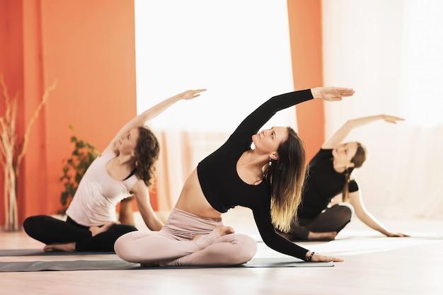 반 연꽃 padmasana 그룹 훈련에서 운동 측면 굽힘을하고 요가 연습 세 여성