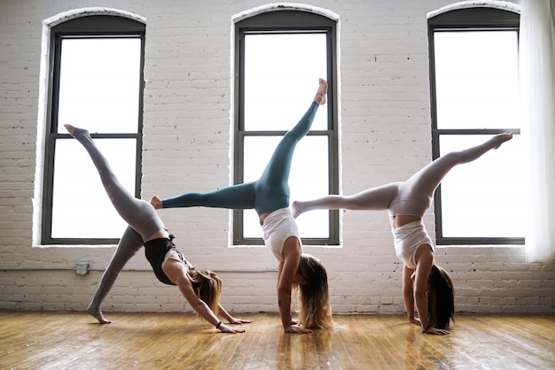 Three women practicing yoga wearing tight yoga outfits in a large room