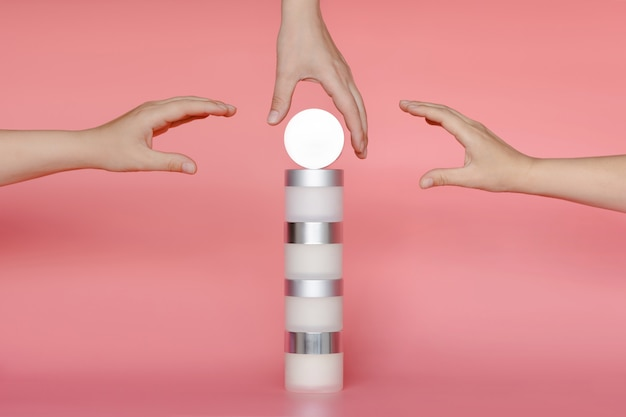 Three women's hands reach for a stack of round cans of cream and serum for face and body.