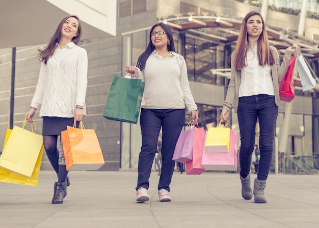 Three women with a lot of shopping bags