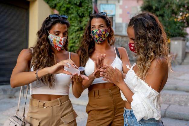 アルコールマスクで手を消毒するマスクをした3人の女性。
