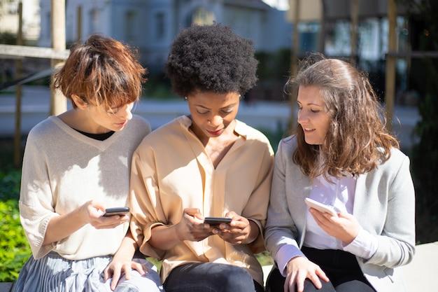 通りに座っているスマートフォンを持つ3人の女性