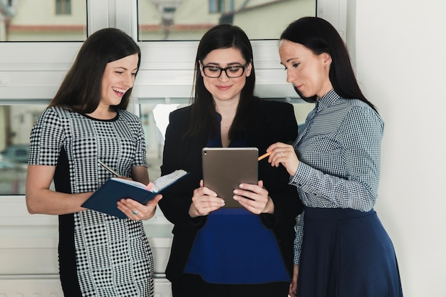 Three women with tablet and documents Free Photo