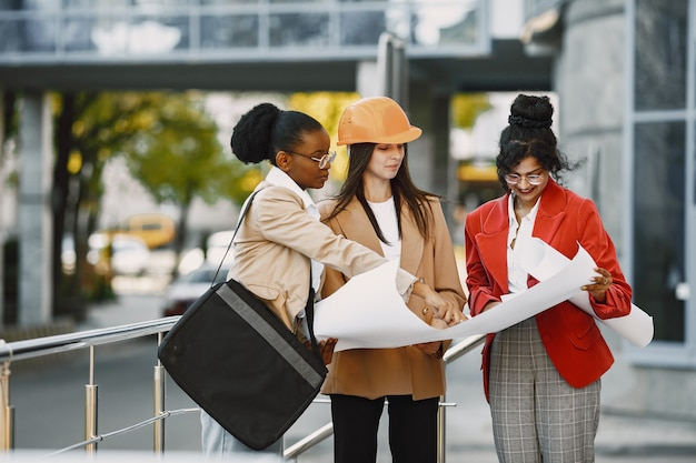 Three women working as architectors on a constraction and making a decision about plan of a building