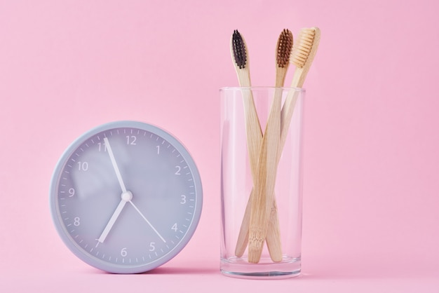 Three wooden bamboo toothbrushes in glass and alarm clock. morning hygiene, dental care concept