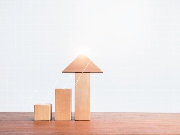 Три деревянных блока шага в виде диаграммы роста со стрелкой вверх на деревянном столе на белом фоне диаграммы сетки с копией пространства, минимальным и эко-стилем. концепция успеха роста бизнеса.