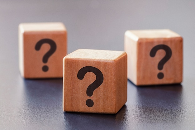 Three wooden blocks with question marks