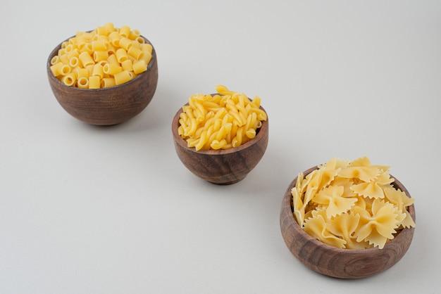 Three wooden bowl full of raw macaroni on white surface