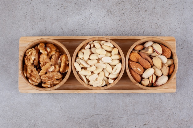 Three wooden bowl of various healthy nuts