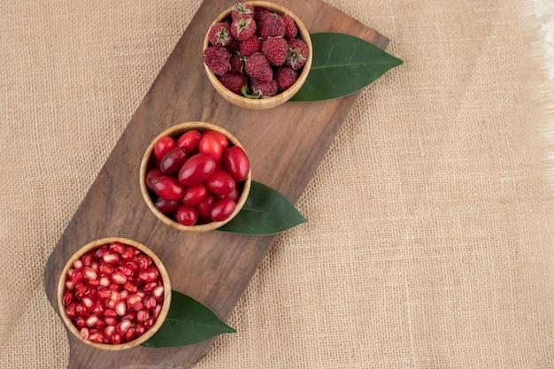 나무 커팅 보드에 딸기로 가득한 세 개의 나무 그릇.